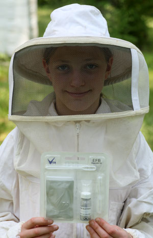 a beekeeper holds an EFB test kit package